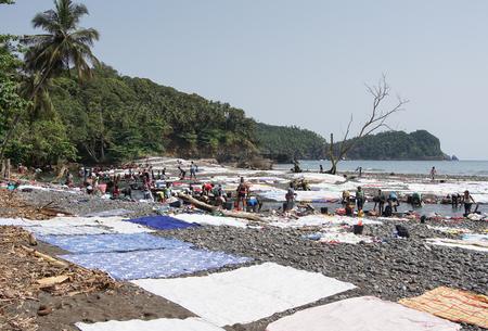 PRAIA MESSIA ALVES, SAO TOME - JANUARY 29, 2017: Women washing clothes on Praia Messia Alves on January 29, 2017 in Sao Tome, Africa Editorial