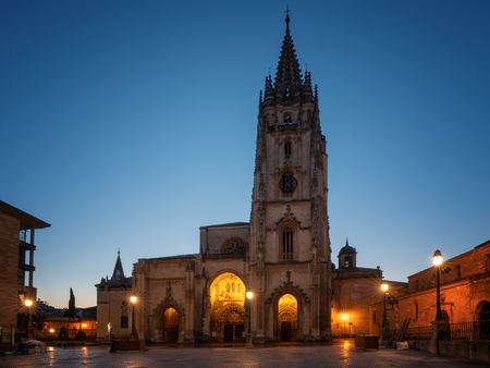 Illuminated cathedral of Oviedo with blue sky at daybreak, Spain
