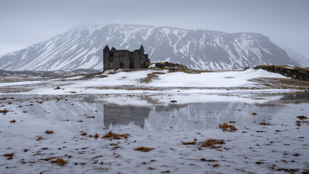 Old farmhouse in front of a mountain, andscape along the southern coast of Iceland at wintertime 免版税图像