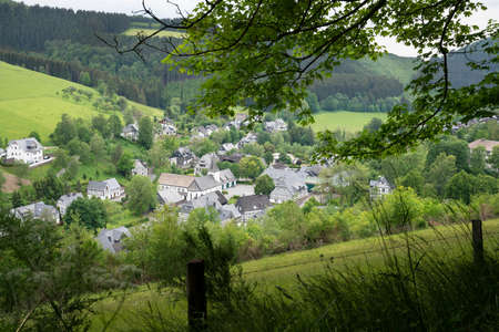 Panoramic image of a small village close to Winterberg with meadows, hills and trees, Sauerland region, Germany