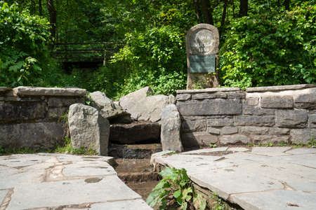 Spring of the river Ruhr with memorial stone and surrounded by trees, Winterberg, Sauerland, Germany