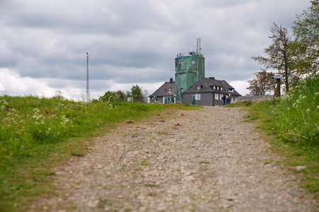 WINTERBERG, GERMANY - JUNE 7, 2020: People on a hiking trail crossing the peak of the Kahler Asten, most famous mountain of Sauerland region on June 7, 2020 in Germany