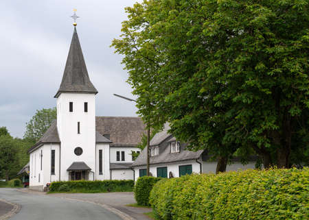 View along the central street of the Sauerland village Westfeld with parish church, old buildings and tree, Schmallenberg, Germany
