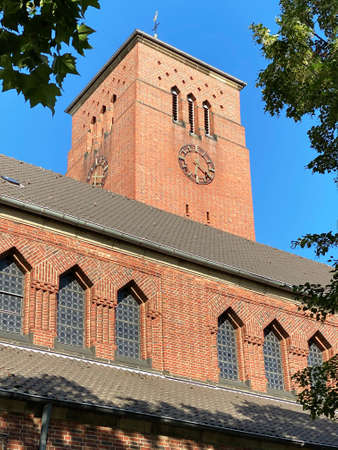 Close-up image of the parish church of Cologne Holweide against blue sky and tree leafs, Germany