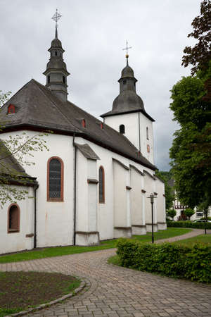 View along a footpath to the parish church of the Sauerland village Oberkirchen, Schmallenberg, Germany