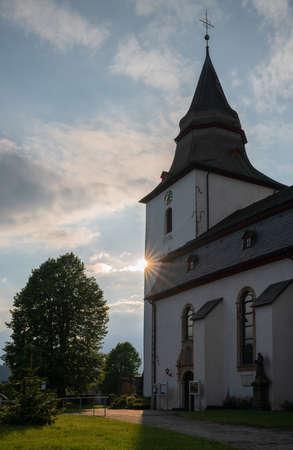 Atmospheric image of the Parish church of Winterberg at sunset with evening sun Stock Photo