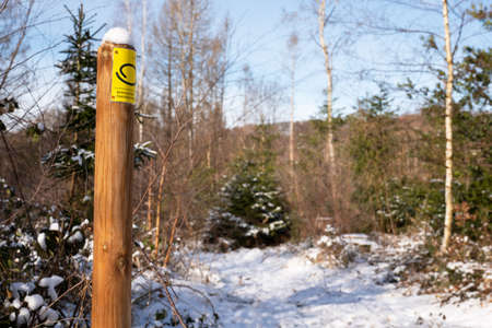 LINDLAR, GERMANY - FEBRUARY 14, 2021: Long distance hiking trail Bergischer Panoramasteig during winter with focus on the typical waymark on February 14, 2021 in Germany