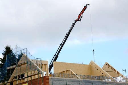 crane parts: Gr�a levanta partes del techo en la c�scara de ladrillo
