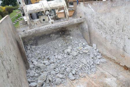 bagger: Bauschutt wird von Bagger in Sammelcontainer geschuettet