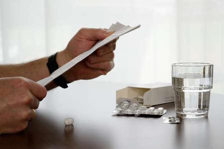 Person liest Packungsbeilage, am Tisch sind Tabletten und Glas Wasser Stock Photo
