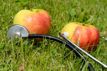 pome: Two apples lying in the grass combined with a stethoscope Stock Photo