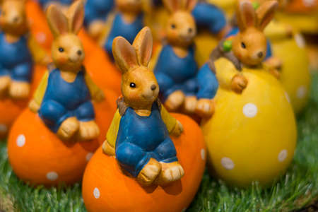 vernal: Numerous colorful ceramic Easter bunnies sitting on colorful Easter eggs Stock Photo