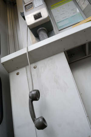 forwarding: In a phone booth telephone receiver hangs freely
