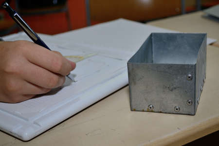 sheet metal: Skilled worker distinguishes technical plan for metal lid Stock Photo