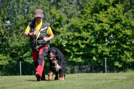 marched: older dog owner marched briskly with her dog during dog training