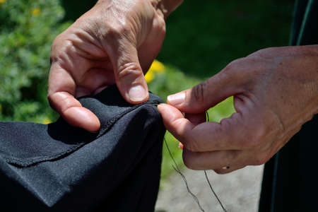 sewn up: Person sewn garment, close up of hands, needle and thread