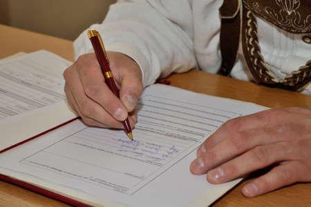 fashionably: fashionably dressed man signing document - closeup Stock Photo