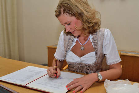 marriage certificate: Bride signing in costume at the registry office marriage certificate