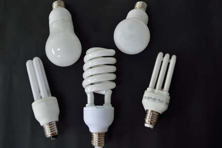 energy use: Five energy saving light bulbs on a black