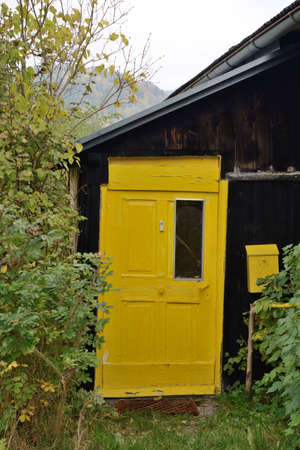 immovable: glowing yellow door in an old wooden house Stock Photo
