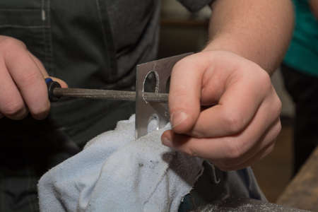 cuttings: Person polishes with round file in a vice jammed piece of metal Stock Photo