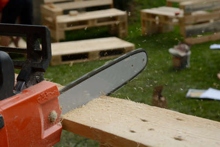 repairer: Person with chainsaw sawed wooden board