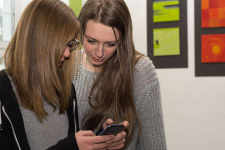 Teenager showing each other on mobile phone Interesting Stock Photo