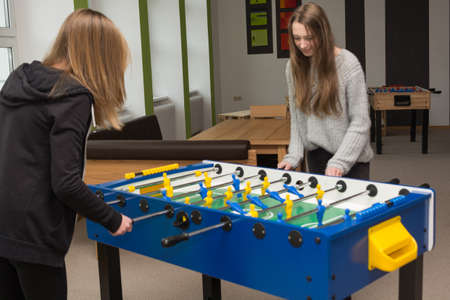 assert: Two teenage girls playing table football