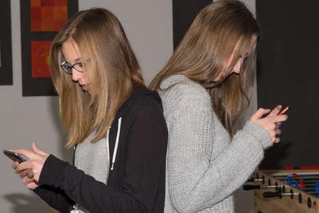 comunicación escrita: Sin decir una palabra - Dos adolescentes con su tel�fono celular Foto de archivo