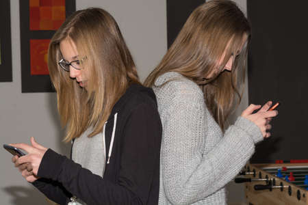 written communication: Without saying a word - Two teenagers with their cell phone Stock Photo