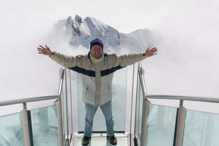 nowhere: Man is happy on the stairs to nowhere on the Dachstein - austria