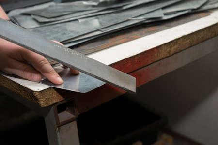 buffing: Artisan polishes sharp metal edge Stock Photo