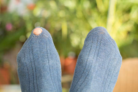 thrifty: Toe looking through hole in a blue sock