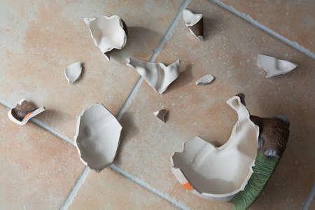 obsolescence: decorative ceramics figure is broken on tiled floor