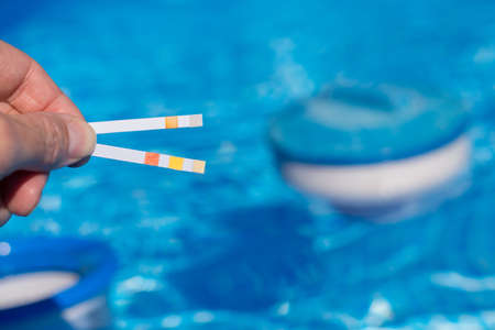 bathwater: Person measures in the pool with test strips important values