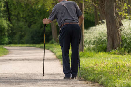 gerontology: frail man walking with difficulty with walking sticks