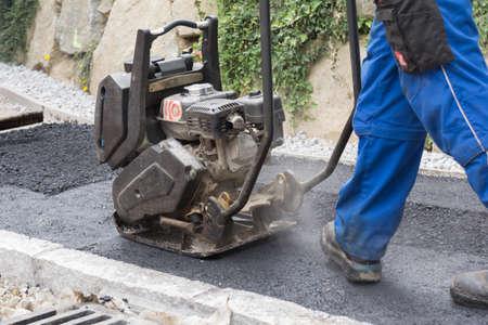 asphalting: Construction worker with vibration plate at sidewalk asphalting