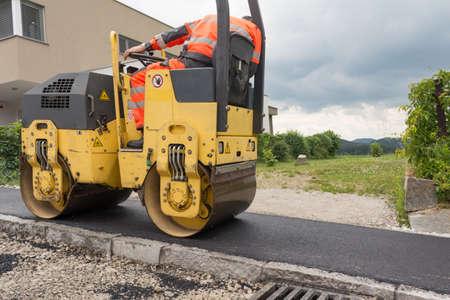 roller compactor: Worker at asphalting works with road roller