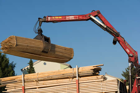 gripper: Truck crane lifts with gripper timber from the truck transporter Stock Photo