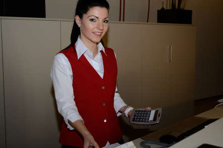 Hotel assistant checked with calculator documents