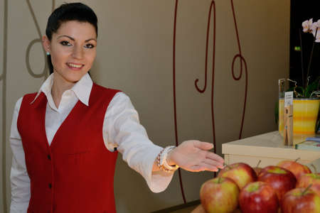 young receptionist pointing at apples for you Stock Photo