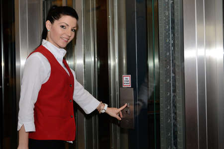 jobholder: Receptionist brings to host the elevator Stock Photo