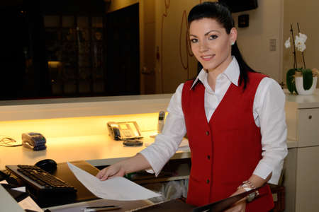 jobholder: young hotel assistant classifies documents in wallet Stock Photo