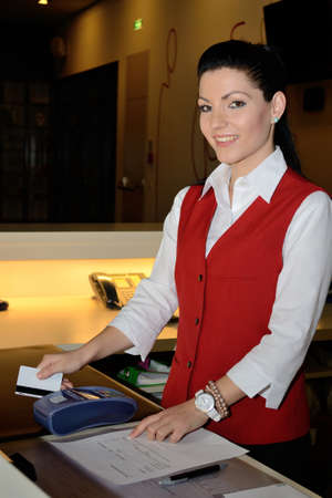 jobholder: young woman with mobile hotel management Debit