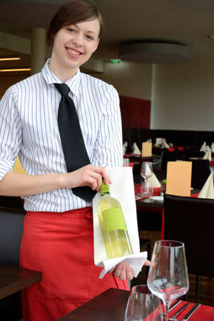 jobholder: hotel assistant presented with a loving smile the wine bottle