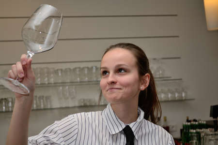 young restaurant assistant checked wineglass