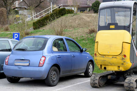 onsite: Excavator uses parking next to cars Stock Photo