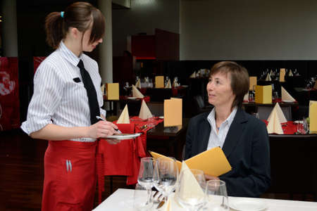 young Restaurant assistant takes at the table when guests order on