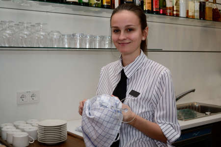 young Restaurant Assistant dries glasses