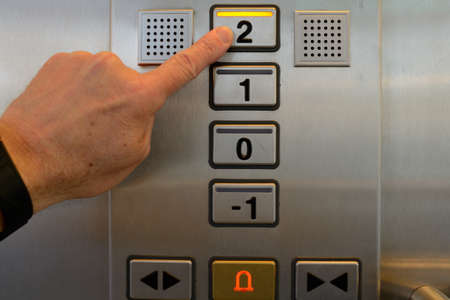 second floor: Finger presses the elevator button on the second floor